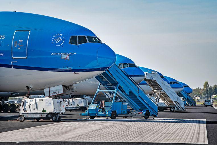 De KLM-vloot op Schiphol is nog altijd hemelsblauw, maar donkere wolken pakken zich boven het bedrijf samen. Beeld