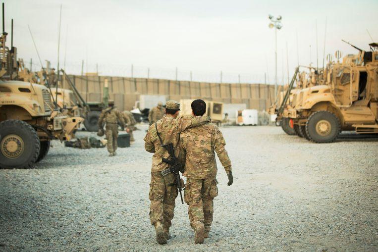 Een Amerikaanse soldaat heeft op legerbasis Gamberi een arm om een Afghaanse tolk heen geslagen. Nu het Amerikaanse leger zich uit Afghanistan terugtrekt, worden de Afghaanse tolken geëvacueerd.  Beeld Reuters