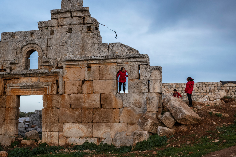 Syrische kinderen spelen in de ruïnes van Al-Kfeir, een voormalig Byzantijns handels- en landbouwcentrum. Beeld NYT/IVOR PRICKETT