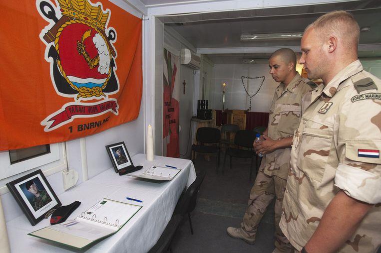Nederlandse militairen staan stil bij het condoleanceregister van Korporaal der Mariniers Jeroen Houweling en Marinier der eerste Klasse Marc Harders op de basis in Tarin Kowt. Foto ANP/Defensie Beeld