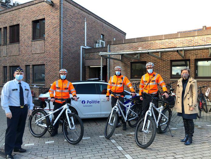 De korpschef Stéphan Gilis (links op foto) en de burgemeester van Tienen Katrien Partyka (uiterst rechts) overhandigen de fietsen aan Kim, Dave en Kevin van het fietsteam van de PZ Getevallei.