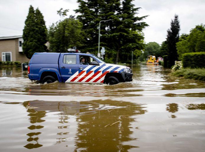 Koninklijke Marechaussee rijdt door een ondergelopen straat nadat een dijk langs het Julianakanaal is doorgebroken. Het water heeft een groot gat geslagen.