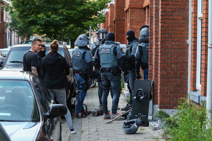 Een arrestatieteam van de politie doet een inval in de bewuste woning aan de Ampèrestraat in Schiedam.
