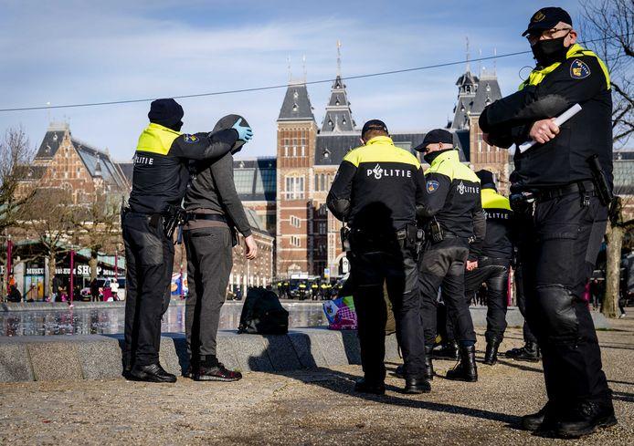 Een man wordt gefouilleerd door politieagenten op het Museumplein.