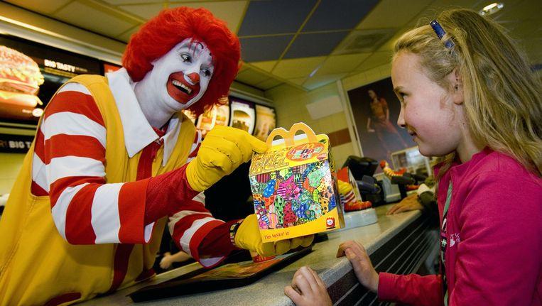 Ronald McDonald overhandigt een Happy Meal aan een meisje. © ANP Beeld