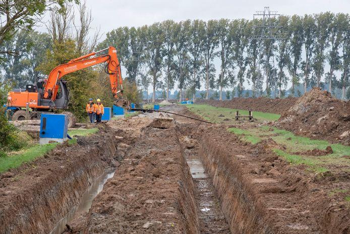 Ten behoeve van de ondergrondse hoogspanningsleiding worden er sleuven gegraven, zoals hier in de Wageningse Vallei.