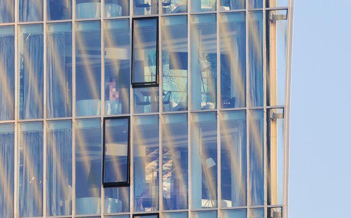 Voorbijgangers zien hoe hotelgasten achter de glazen gevel in hun kamer naakt recreëren