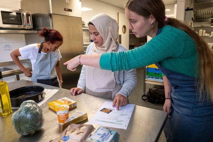 Senait en Amiea leren met hulp van stagiaire Lavina, bij in de Elburgse keuken.