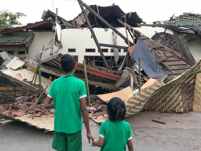 Twee kinderen kijken naar de puinhopen van wat tot voor kort hun woonruimte was.