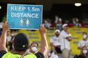 Een steward in Duitsland maant de supporters aan om afstand te houden.