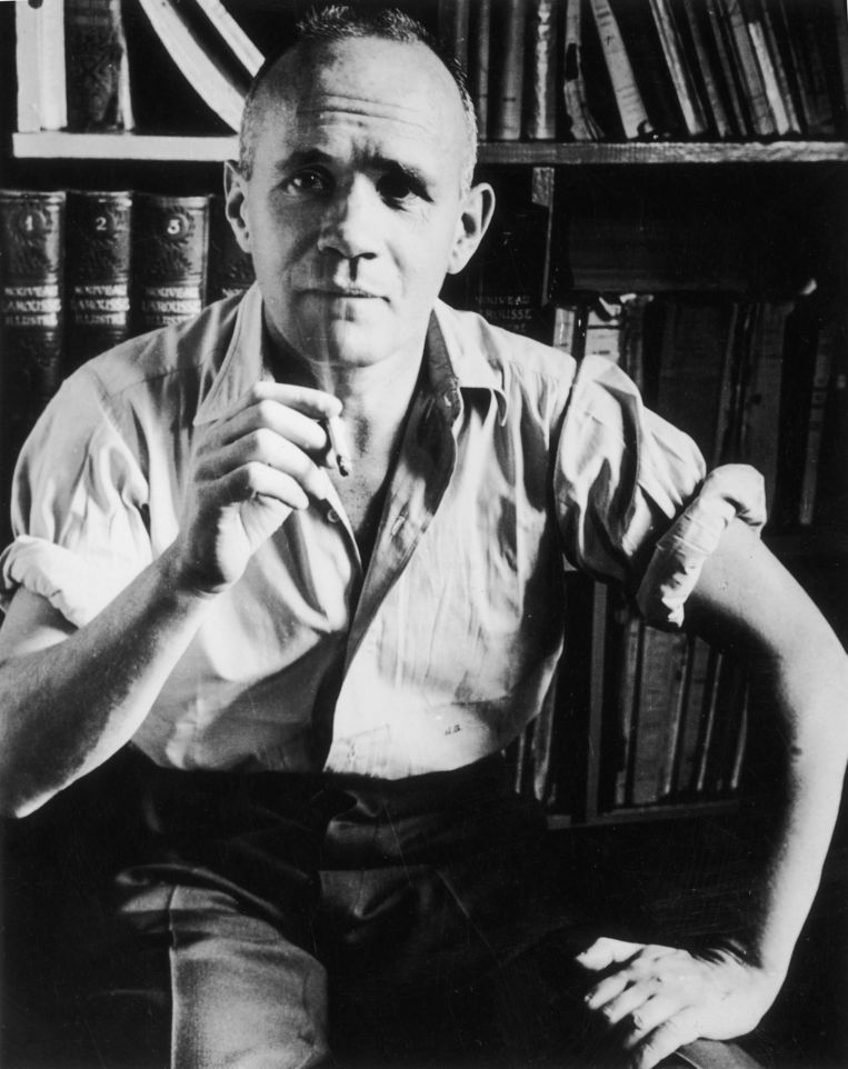 circa 1950:  Portrait of French author Jean Genet (1910 - 1986) sitting in front of a bookshelf with his shirt sleeves rolled up, holding a cigarette.  (Photo by Hulton Archive/Getty Images) Beeld Getty Images
