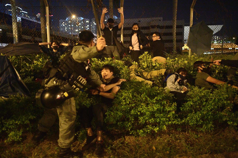 De politie in Hongkong houdt dinsdag studenten aan die proberen te vluchten van de campus van de Polytechnische Universiteit.   Beeld AFP