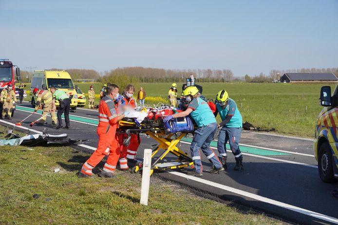 Een van de slachtoffers wordt naar de ambulance gebracht op de Maas en Waalweg bij Afferden.