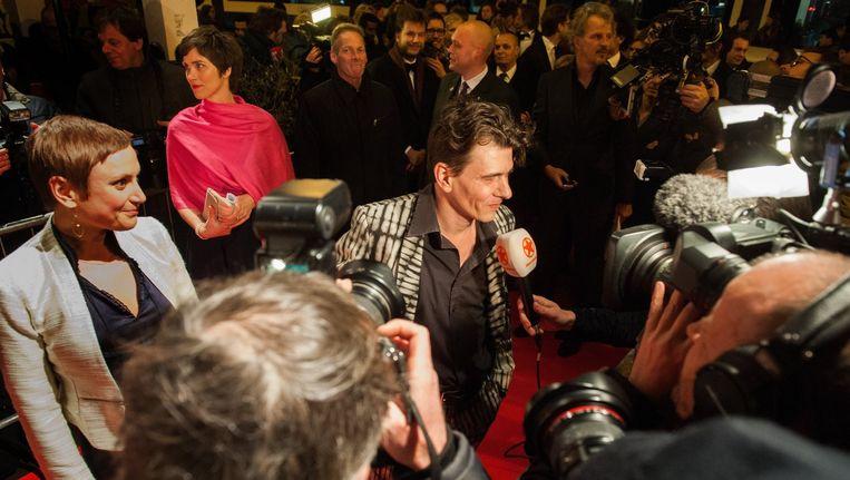 De schrijvers arriveren op de rode loper, terwijl de pers elkaar verdringt. Dimitri Verhulst baant zich als een rockster een weg door de menigte met zijn vriendin Céline. Beeld PHOTO_NEWS