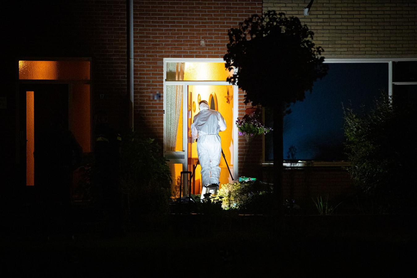 Forensisch rechercheurs doorzoeken de woning waar het lichaam werd aangetroffen.