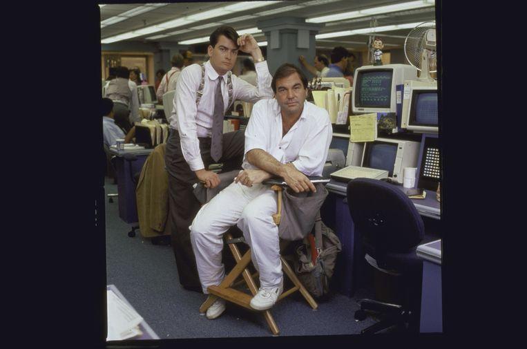 Oliver Stone (rechts) met Charlie Sheen op de set van 'Wall Street' (1987). Beeld Getty