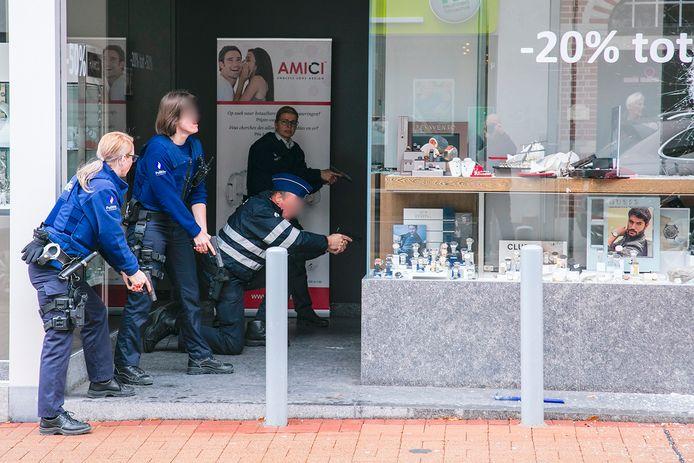 Politiemensen met getrokken wapens aan de juwelierszaak, waar de daders nog binnen zijn.