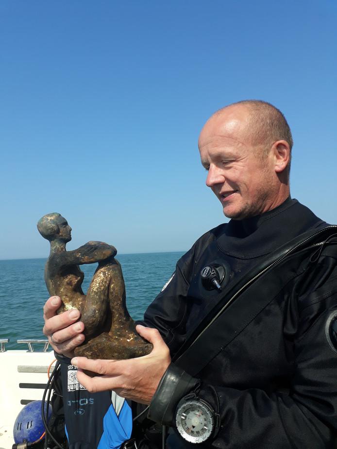 Duiker Leon Joosse met het bronzen beeld van een geknielde vrouw, van beeldhouwer Lambert Zijl, uit het wrak van passagiersschip Christiaan Huygens.