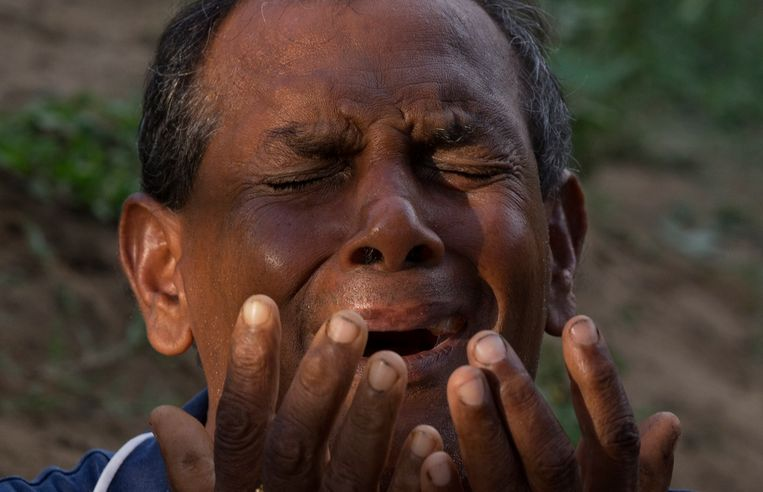 Een man bidt tijdens de begrafenis van een van de slachtoffers in Negombo.  Beeld AP