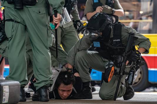 Agenten slaan bij betogingen in Hongkong een betoger in de boeien.