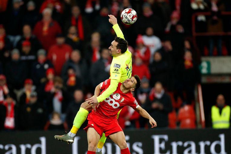 AA Gent-middenvelder Sven Kums vliegt de lucht in na een duel met Gojko Cimirot van Standard. Beeld Photo News