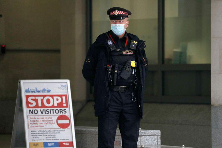 Een agent bewaakt de toegang van St Bartholomew's, het Londense ziekenhuis waar prins Philip behandeld wordt. Beeld AFP