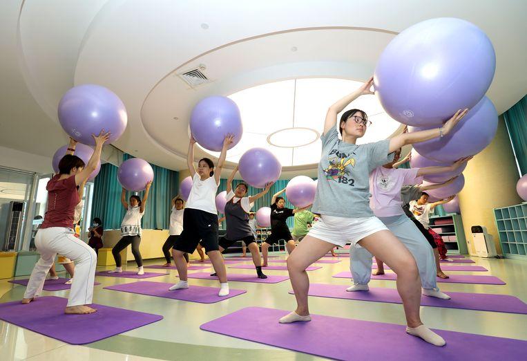 Zwangere vrouwen doen fitnessoefeningen in de Chinese stad Shijiazhuang. Beijing moedigt zwangerschappen weer aan. Beeld Getty