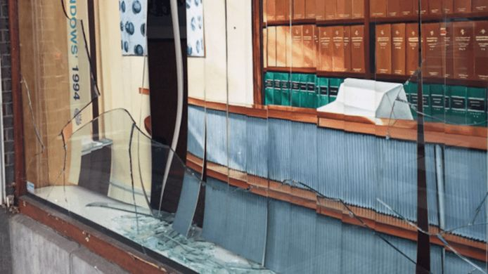 Een van de vernielde ruiten van het advocatenkantoor.