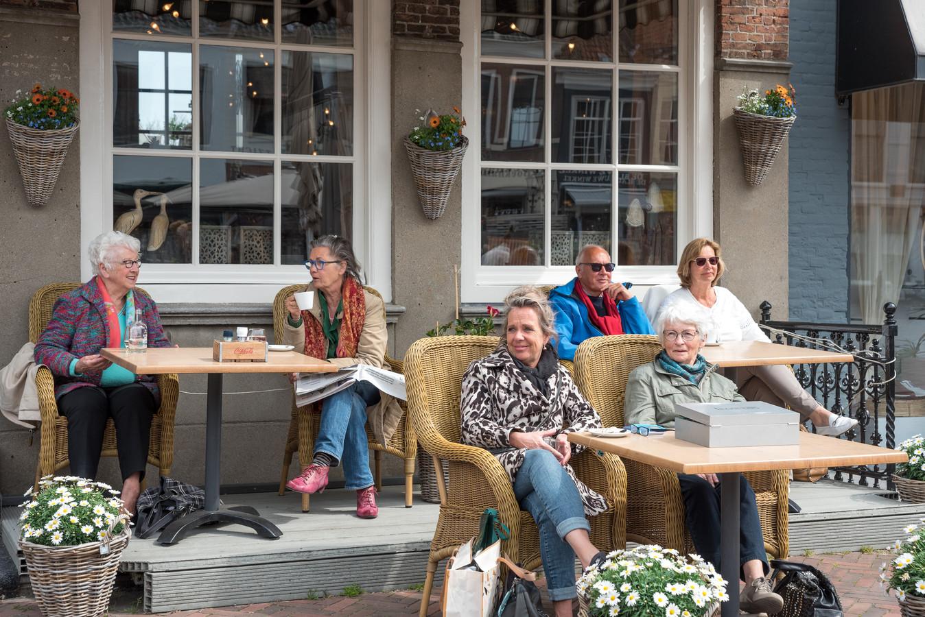 """Vaste gasten claimen gelijk om 12.00 uur hun plek bij restaurant De Beuze in Zierikzee. Links bij raam Leny Born (l) en Bea Poppe, middenvoor dochter Marjo (l) en moeder Ina Giljam (r), en rechts bij het raam Maarten en Jolande Hardon. Marjo en Ina genieten vooral van het mensen kijken. ,,Als we in de stad zijn, gaan we altijd hier bij De Beuze zitten."""""""