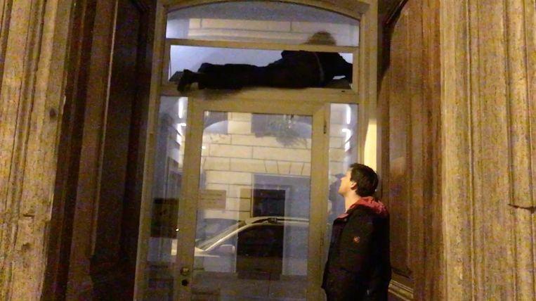Wannes Deleu kruipt door een openstaand klapraam het hotel binnen. Beeld Kamiel De Bruyne