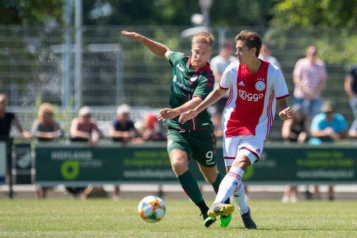 Tom van Weert (links) in duel met Ajacied Victor Jensen tijdens een vriendschappelijke wedstrijd tussen Aalborg en Ajax.