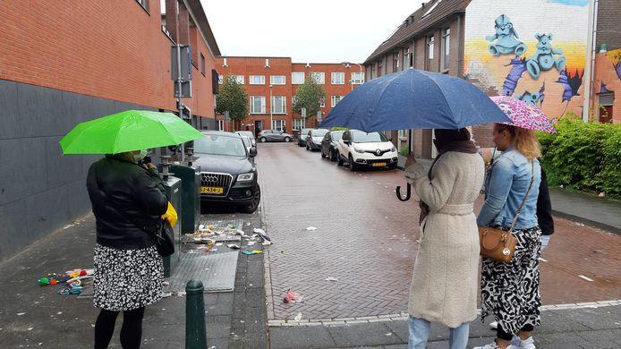 Bewoners kijken vol walging naar het afval dat is blijven liggen nadat de containers zijn geleegd. ,,Als de zon schijnt, ruiken wij de stank binnen.''