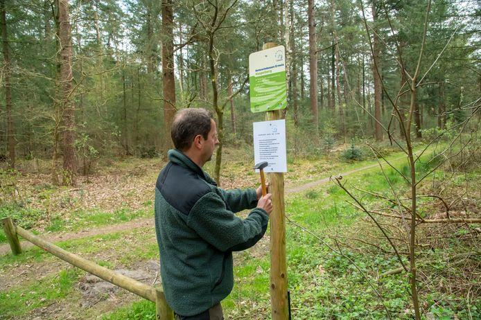 Boswachter Henk Jan Zwart timmert nieuwe instructies langs de toegangsweg tot het bos aan de Staringlaan. Tot 20 juni mogen honden in de Ermelose natuurgebieden niet meer los rondlopen.