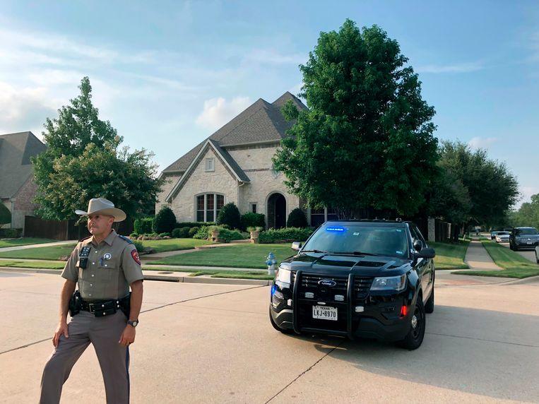 Een politieagent voor de ouderlijke woning van Crusius in Allen, Texas. Beeld AP