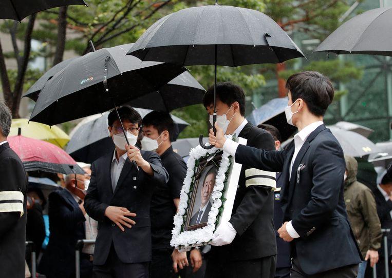 Het portret van Park Won-soon wordt meegedragen tijdens zijn begrafenisceremonie. Beeld AP