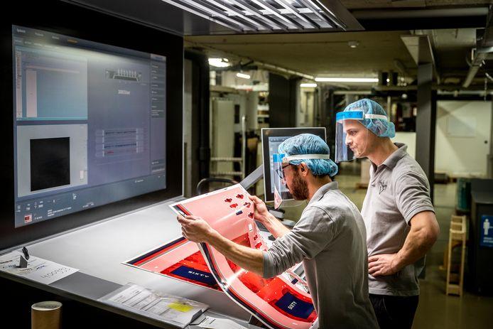 Medewerkers Robert van Eijk (links) en Joost Middendorp inspecteren een drukvel bij een offsetpers van drukkerij Vrijdag.