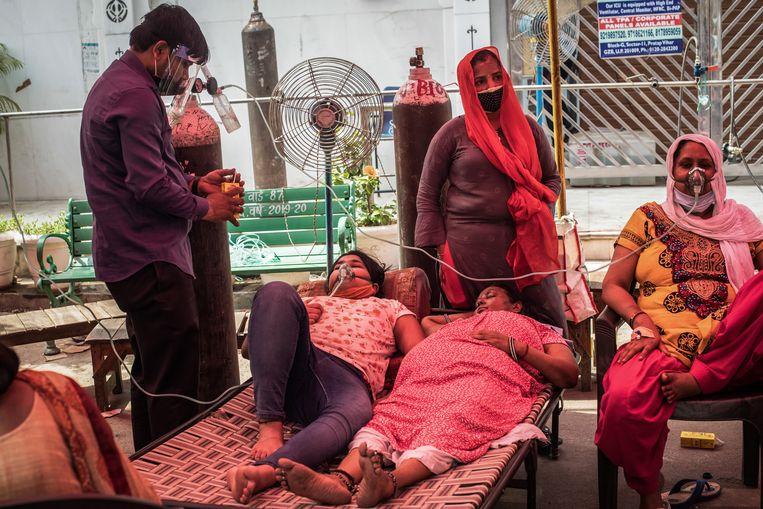 Coronapatiënten in de staat Uttar Pradesh krijgen op straat zuurstof toegediend voor de deur van een tijdelijke kliniek.  Beeld Getty Images