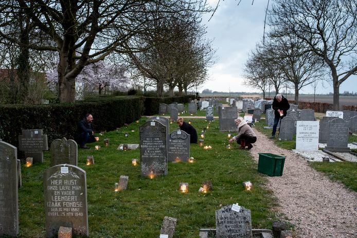 René en Rosalinde van Ingen Schenau zetten samen met Ingrid en Tommy Katilas vlnr waxinelichtjes bij de graven op de begraafplaats van Zonnemaire. Alle zerken waar een bordje bij hangt worden dit jaar vernietigd door de gemeente.