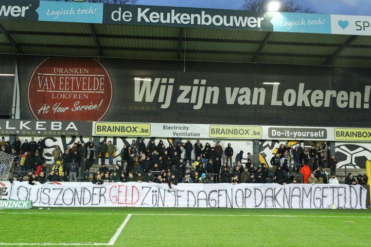 De supporters van Sporting Lokeren maken hun ongenoegen kenbaar, tijdens de wedstrijd tegen Virton vorig weekend.  Beeld BELGA