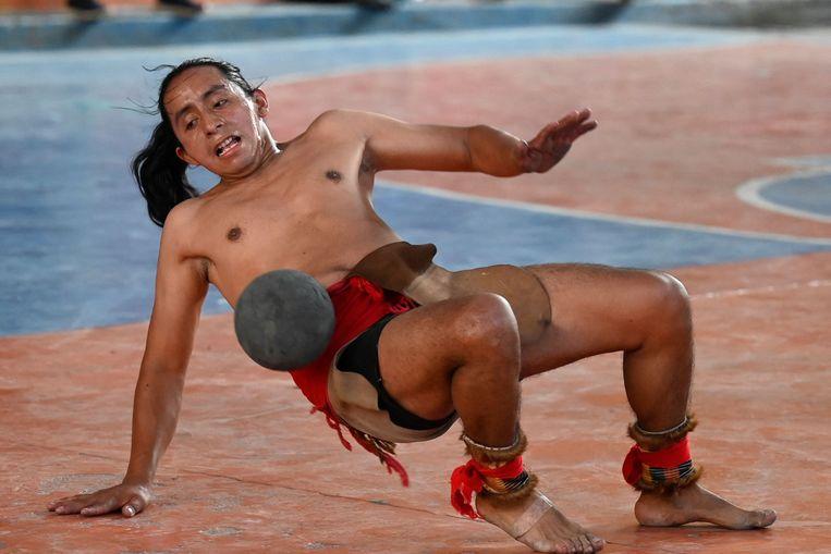 Een Guatemalteek neemt deel aan een potje Meso-Amerikaans balspel in San Juan La Laguna, Guatemala. Bij dit duizenden jaren oude spel, dat door de Azteken en de Maya werd gespeeld, mogen deelnemers de bal niet met hun armen of benen aanraken, alleen met hun heupen en bovenlijf. De doelen zijn tegen de muren bevestigde stenen ringen. Beeld AFP