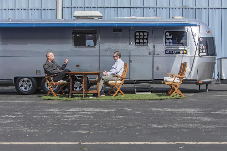 Tom Hanks (l) voor zijn immense Airstream-caravan die binnenkort geveild wordt.