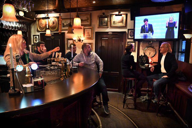Oktober2020: in dit café in Den Bosch wordt aandachtig gekeken naar een persconferentie   van Mark Rutte over strengere coronamaatregelen.  Beeld Marcel van den Bergh