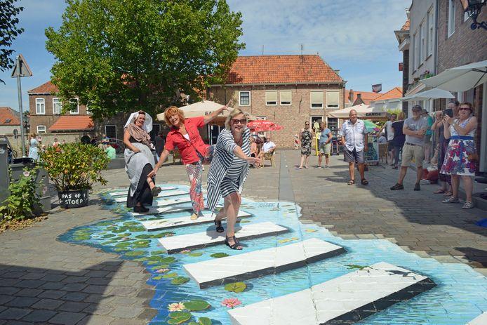 Wethouder Ankie Smit (vooraan) opende 6 augustus samen met kunstenaar Inge de Groot (midden) en initiatiefnemer Christel Brunger (in klederdracht) het silly walks zebrapad op het Zierikzeese Plein Montmaertre.