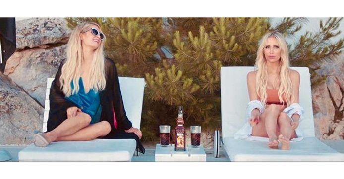 Paris Hilton en  Anouk Matton, met tussen hen, een fles en twee glazen Omerta Rum.