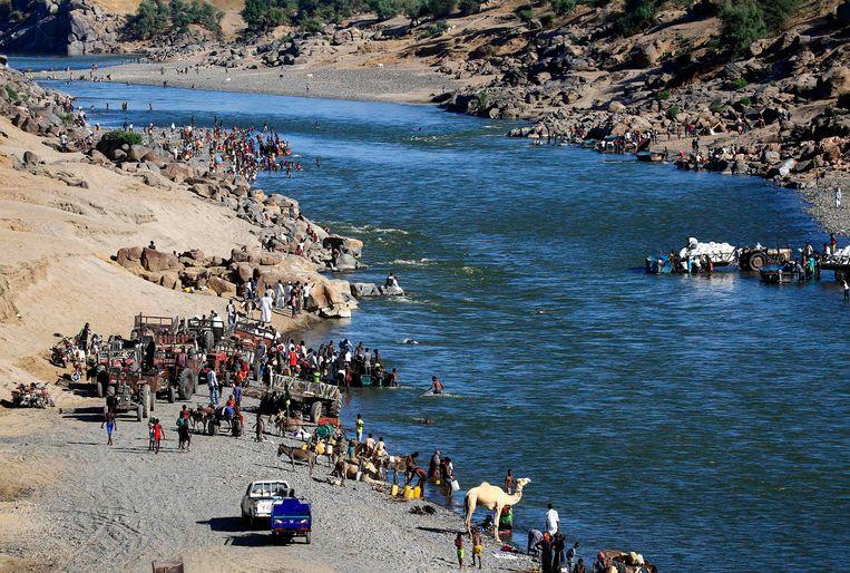 Ethiopische vluchtelingen uit Tigray steken de Setit over naar Soedan aan het begin van de burgeroorlog vorig jaar. Door de regentijd is het rivierwater onlangs enorm gestegen en is de gevaarlijke Setit amper meer over te steken.  Beeld AFP