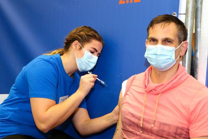 Marco Tichelaar krijgt als eerste een coronavaccin in sporthal De Hoefslag in Gorinchem. Verpleegkundige Dominique Groeneveld dient dit toe.
