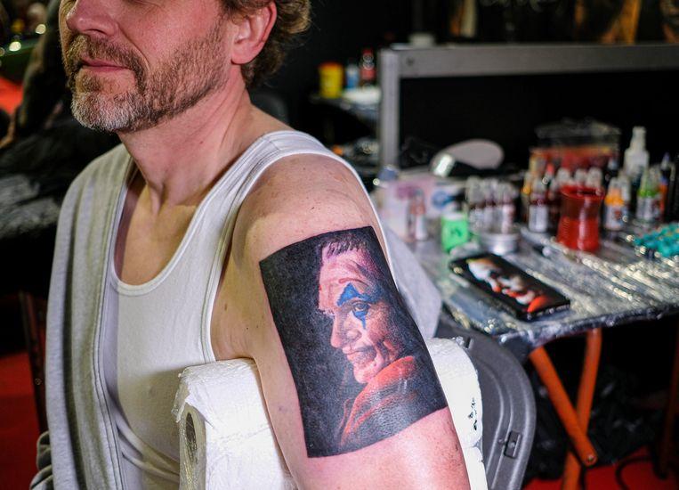 Man met 'the Joker' op de arm getatoeëerd, tijdens de International Brussels Tattoo Convention in november. Beeld EPA