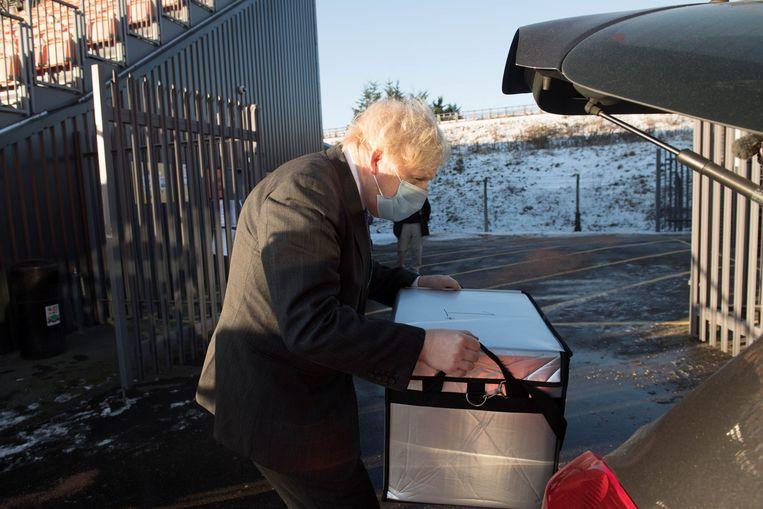 De Britse premier Boris Johnson draagt maandag een tas met het Oxfordvaccin naar een mobiele vaccinatielocatie in Noord-Londen. Beeld REUTERS