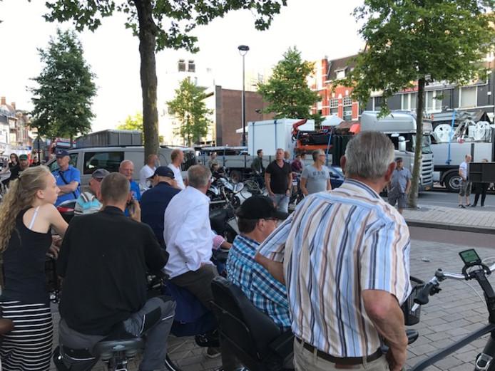 Groepjes Tilburgers kijken geïnteresseerd naar de opbouw van de kermis.