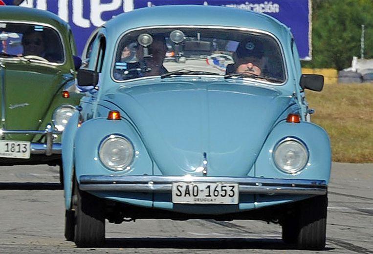 President José Mujica van Uruguay in zijn 27 jaar oude VW Kever. Beeld AFP